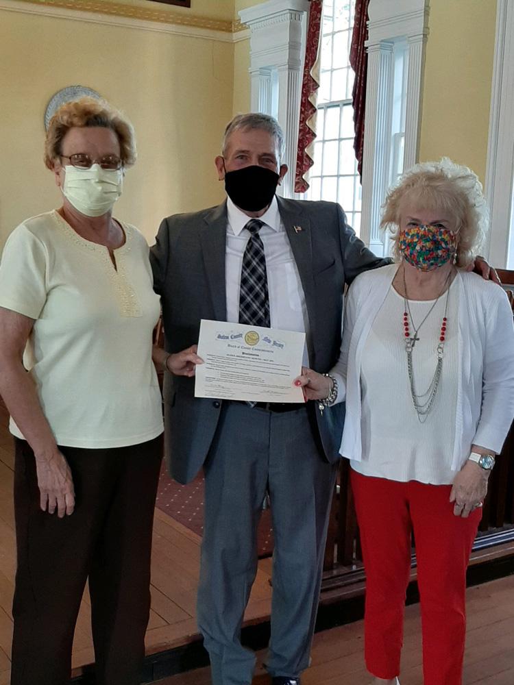Man standing between two older women holding certificate